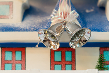 Two silver Christmas bells hanging on a ribbon in front of a model house with scattered winter snow