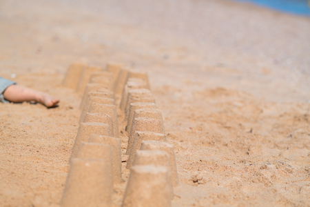 Row of little sand castles on a sandy beach at the edge of the water in a close up view with copy space