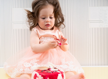 Little baby girl in pink dress holding a cherry from her birthday cake, sitting on table surface against white wall
