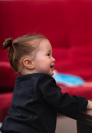 Young smiling baby girl in black shirt, standing with her hands on the table, viewed from her side against blurred red background