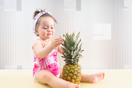 Curious little baby girl playing with the leaves of a big fresh tropical pineapple with an absorbed expression