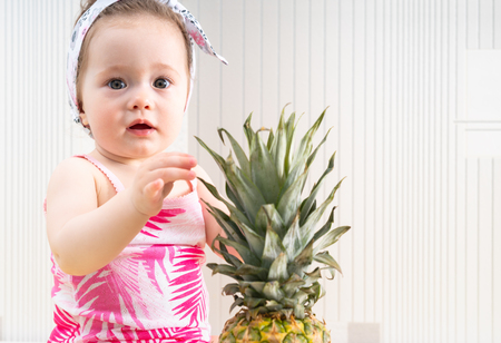 Close-up portrait of cute little baby girl in pink shirt touching leaves of a pineapple and looking at camera with surprised face Stock Photo