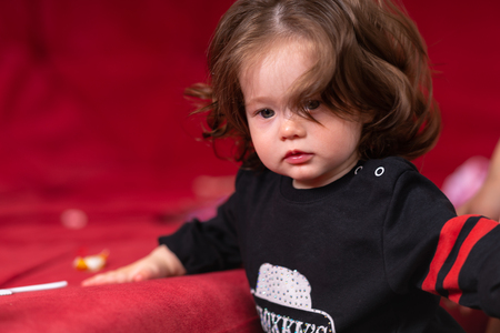 Portrait of beautiful baby girl with brown hair, wearing black shirt, standing with her hand to a couch against red background