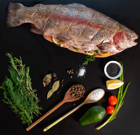 Culinary still life with fresh trout and assorted seasoning including herbs and spices, lemon, tomato, spring onion and avocado pear on a square black background
