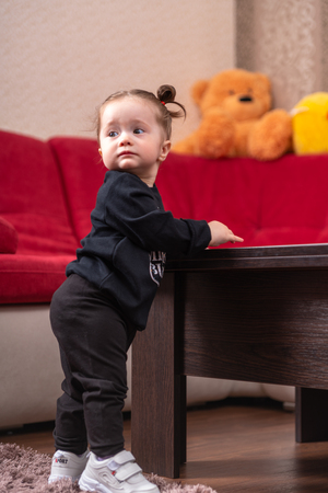 Young baby girl in black learn to walk and leaning on wooden coffee table in living room, looking away. Viewed from low angle in living room interior Archivio Fotografico
