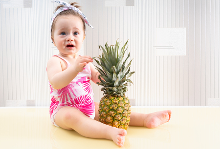 Cute little baby girl sitting on yellow table with huge pineapple in front of her, and touching its leaves with surprised face emotions Stock Photo - 120412698