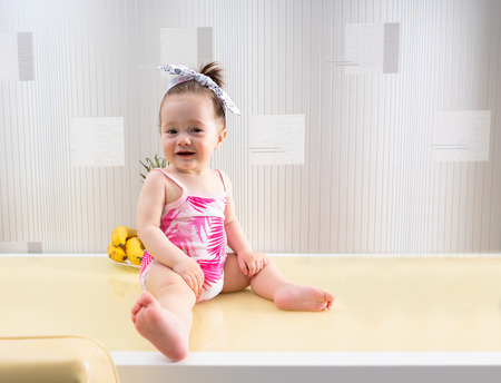 Adorable little girl in a pink romper suit sitting barefoot on a table smiling happily at the camera 版權商用圖片