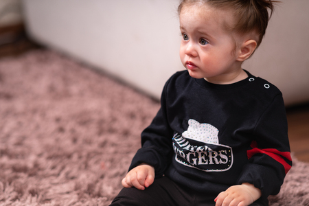 Cute little baby girl in black shirt, sitting on a carpet on floor in living room and looking away. Close-up high angle portrait with copy space Stock Photo