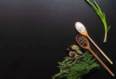 Cooking ingredients with fresh aromatic herbs including rosemary and dill with spices and seasoning in wooden spoons over a black background with copy space Stock Photo