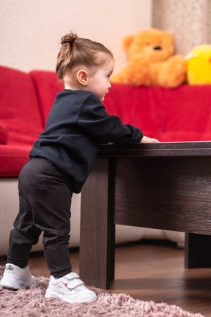 Adorable little baby girl learning to stand balancing holding on to a table indoors in the nursery Stock Photo - 120412713