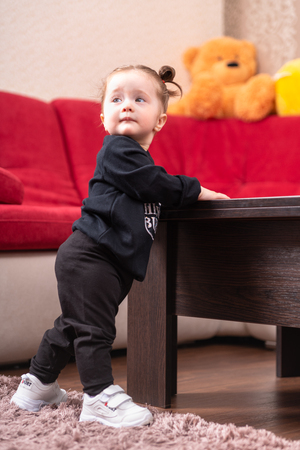 Cute little girl with pigtails supporting herself on a table in the nursery as she learns to stand and walk