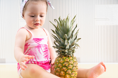 Young and cute baby girl in pink shirt sitting on table surface and looking at big pineapple in front of her Stock Photo - 120412597