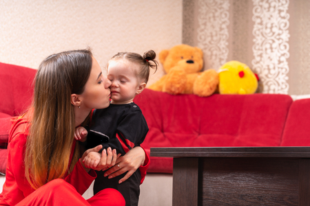 Young mother kissing her little baby girl at home. Red couch and plush toys in background. Viewed from low angle with copy space