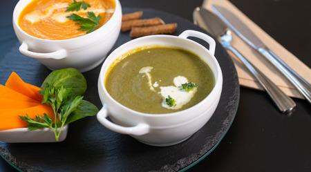 Schüssel leckere Brokkoli-Spinat-Suppe mit einer zweiten Schüssel Butternuss- oder Kürbissuppe dahinter auf einem schwarzen runden Holzbrett für köstliche Vorspeisen zu einem Abendessen a