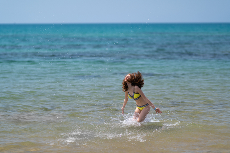 Carefree young woman in a bikini frolicking in the sea tossing her long hair as she splashed through the shallows
