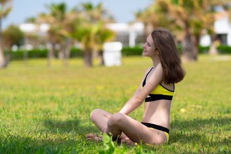 Happy smiling young woman in a yellow bikini enjoying a hot day relaxing cross legged on the grass in the shade of tree in an urban park looking to the left of the frame