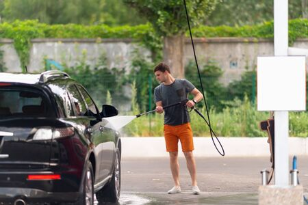 Young man spraying the side of his car with water from a high pressure hose at a car wash facility as he washes his black saloon car.