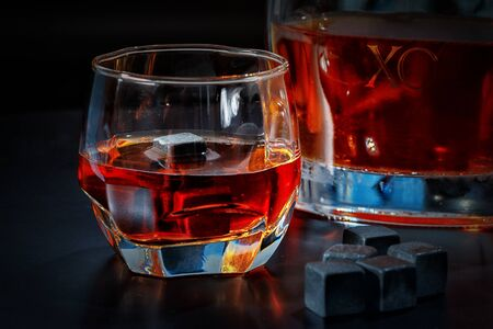 Glowing glass of whiskey with chilling cubes or reusable ice blocks and decanter on a pub counter in a close up view