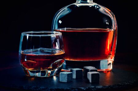 Bar still life with whisky and black shungite chilling cubes or reusable ice blocks against a dark background conceptual of a nightclub or nightlife