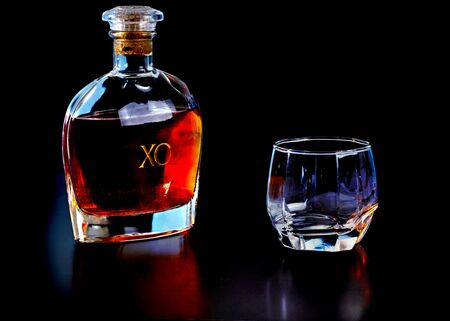 Decanter of matured French cognac with a glass on a black reflective surface with copy space above