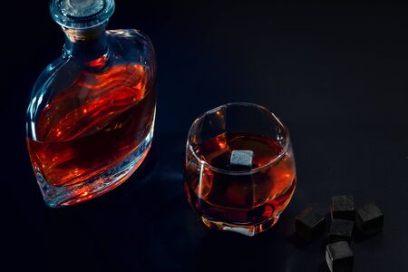 Decanter of mature malt whisky with full glass alongside reusable ice cubes or chilling blocks on a bar counter in a high angle view