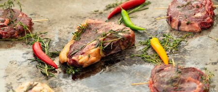 Panorama banner of assorted raw beef steaks with fillet medallions, sirloin and t-bone together with herbs and chili peppers for flavoring on a restaurant kitchen counter