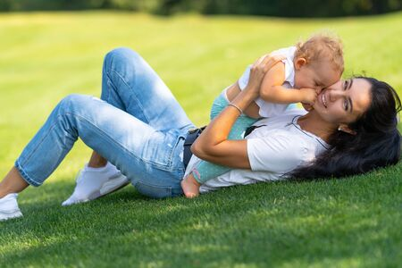 Laughing joyful young mother cuddling her child close to her cheek as they play together on the grass in a tender portrait