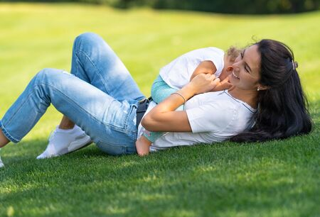 Happy loving young mother cuddling with her baby child in a close embrace as they play together on the grass under a shady tree Stock Photo