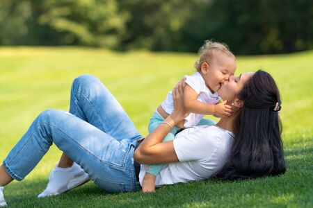 Loving young mother kissing her infant daughter tenderly as they play together on green grass outdoors in the garden in the shade of a tree