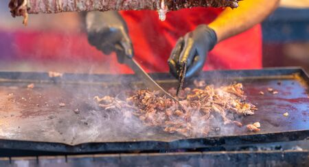 Chef carving seasoned spicy meat from a doner kebab into a heated tray below at a street market or catered event in a close up on his hands