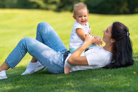 Young mother playing with her happy little baby daughter outdoors on green grass in the garden as the child gives the camera an adorable smile Stock Photo