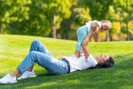 Happy young mum playing with her infant daughter holding her up in the air as they enjoy a hot summer day outdoors in the shade of a tree Stock Photo