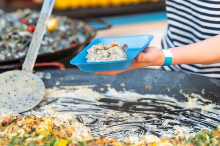 Person using a large ladle to serve a savory pie or quiche into a disposable container for a takeaway meal at an event or street market Stok Fotoğraf