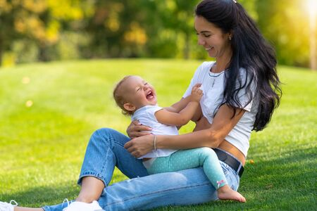 Laughing happy little child with its mother on the grass grabbing her t-shirt to expose the breast for feeding as they sit outdoors on green grass