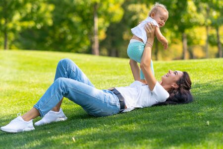 Laughing loving young mother playing outdoors on the grass with her infant daughter holding her up on the air as the child laughs with pleasure