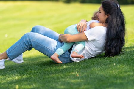 Loving mother hugging her baby child tightly to her chest with a happy tender smile as they play together outdoors on green grass in the garden Stock Photo