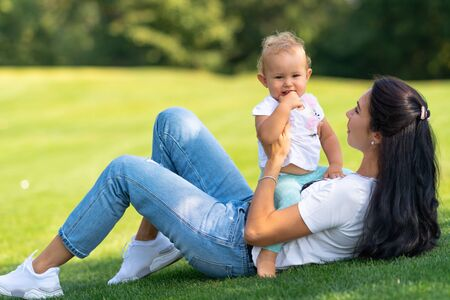 Cute cherubic little baby girl with her Mum smiling happily at the camera as they play together outdoors on the grass in the garden Stock Photo