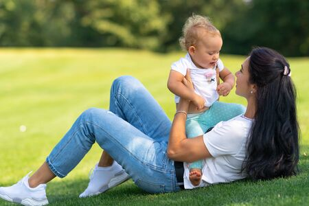 Cute little baby girl with her loving mother as they play together outdoors on a hot summer day on the grass under a shady tree