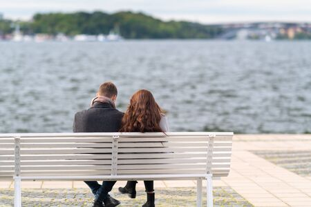 Couple sitting on a bench overlooking choppy water on a cold windy autumn day in their thick coats in a rear view