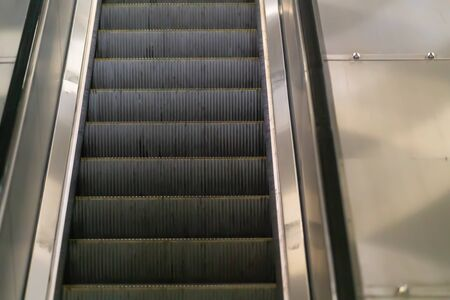 Close up on the treads of an empty moving escalator in a subway or mall with reflection on the steel sides