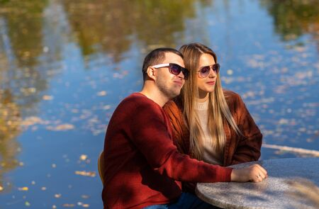 Romantic young couple dating in an autumn park seated at a table at an outdoor restaurant overlooking a lake Stock Photo
