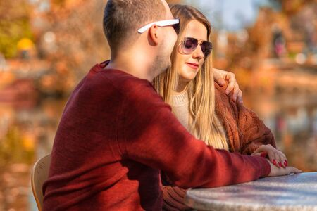 Young couple on a romantic date in autumn sitting arm in arm at an outdoor restaurant table enjoying the evening sunshine