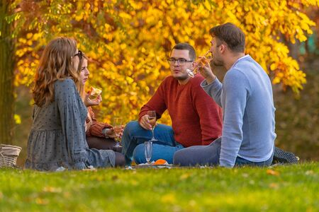 Young friends celebrating with champagne at a picnic in an autumn park with colorful yellow foliage on the trees