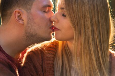 Young couple in love enjoying a tender kiss in a close up on their faces as their lips touch