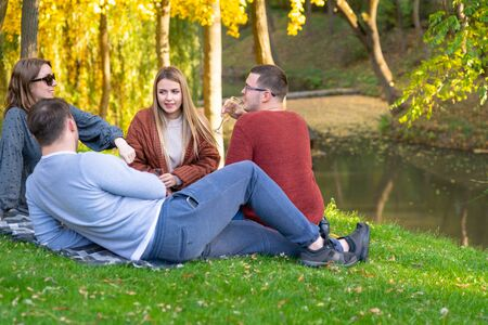 Two couples spending a relaxing day picnicking on the grass in a park in autumn with colorful fall leaves on the trees