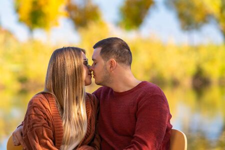Young man and woman deeply in love seated arm in arm preparing to kiss against an outdoor autumn background