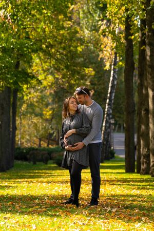 Young couple with pregnant wife standing in a park in autumn in a close embrace cradling her stomach as they bond with their unborn child Stok Fotoğraf