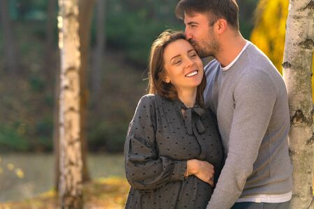 Happy young pregnant woman cuddling with her husband as they lean against a tree in a park in evening light