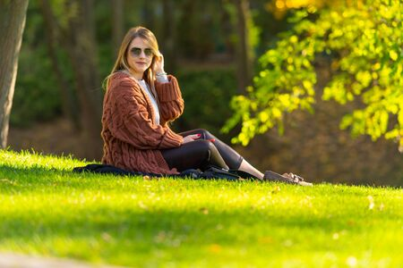 Pretty trendy young woman relaxing in an autumn park sitting on the grass in the evening sun turning to look at the camera