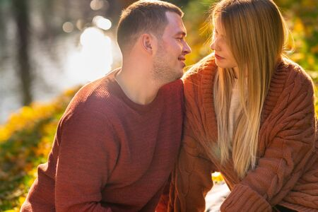Loving young man smiling tenderly at his wife or girlfriend as they send a relaxing evening alongside a lake in an autumn park